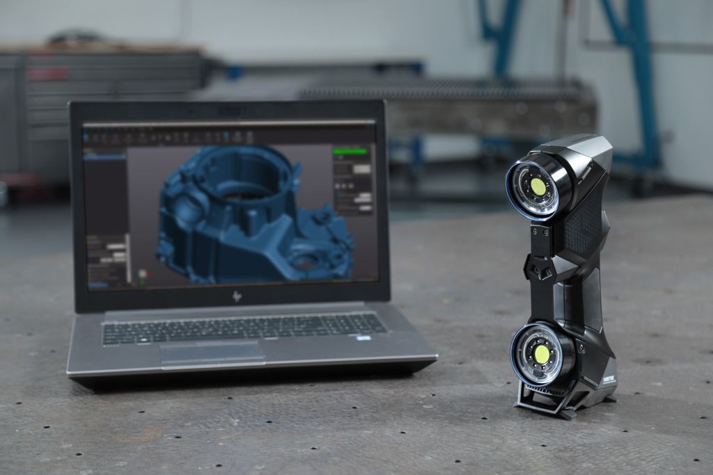 Portable 3D scanner and laptop showing the scan of an automotive die casting part shown in a 3D software