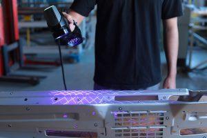 Creaform HandySCAN BLACK blue laser 3D scanner on a sheet metal Mustang dashboard for dimensional inspection.