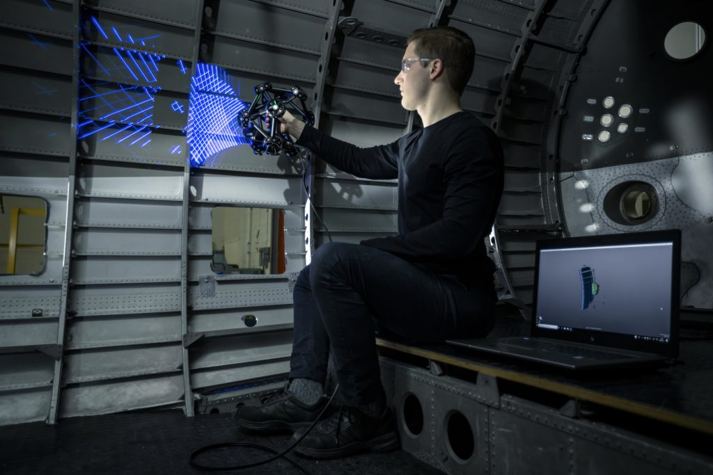 Metrology technician operating a handheld 3d laser scanner on an aerospace interior for quality control purposes