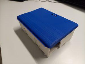 White plastic moustrap with blue lid on desk