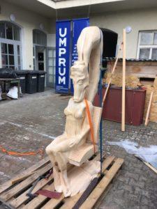 Reprodução escalonada da estátua sentada em um palete de madeira