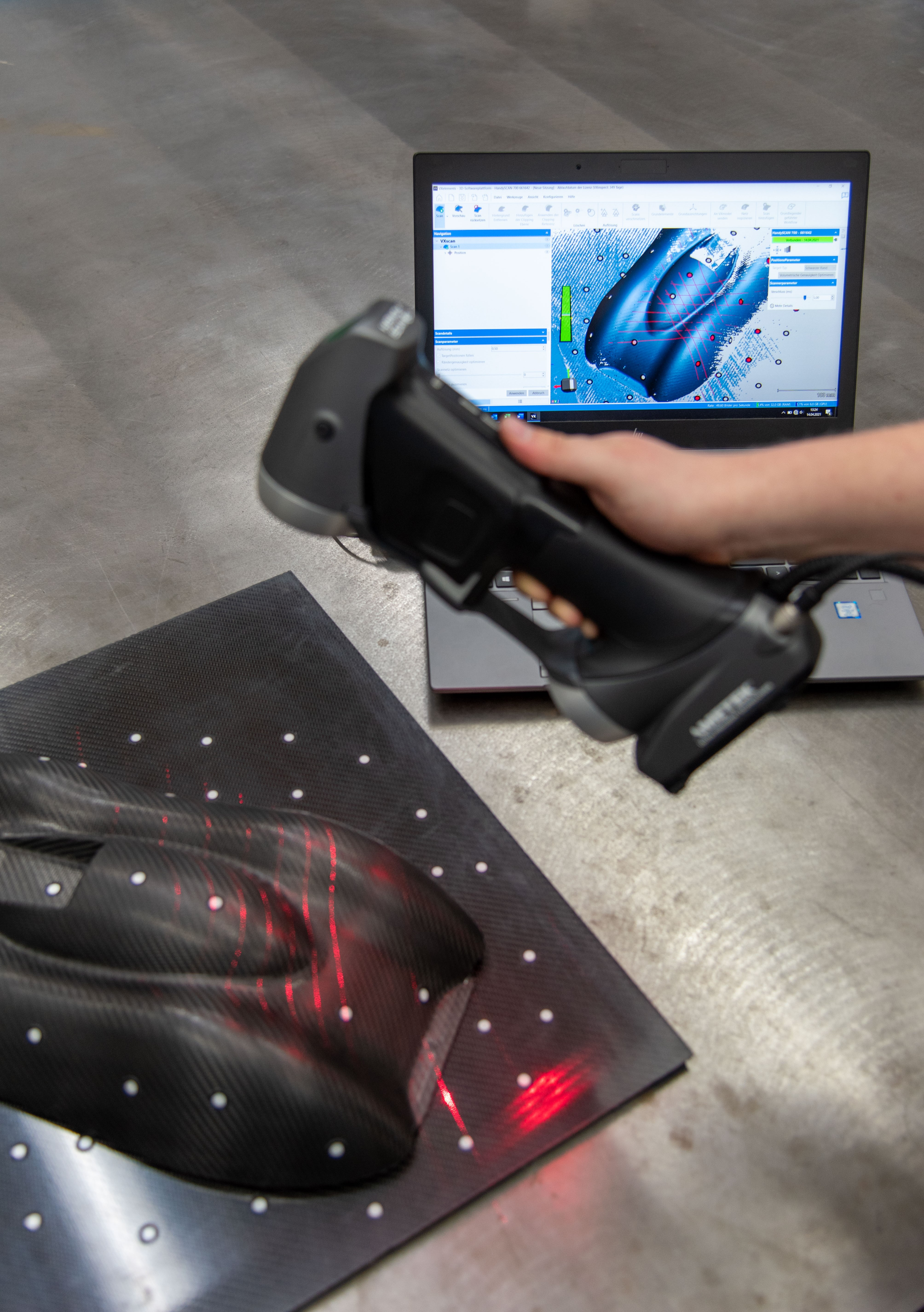Employee using HandySCAN 3D SILVER series scanner to scan a carbon fber car part on a table in front of laptop displaying in real-time in VXelements
