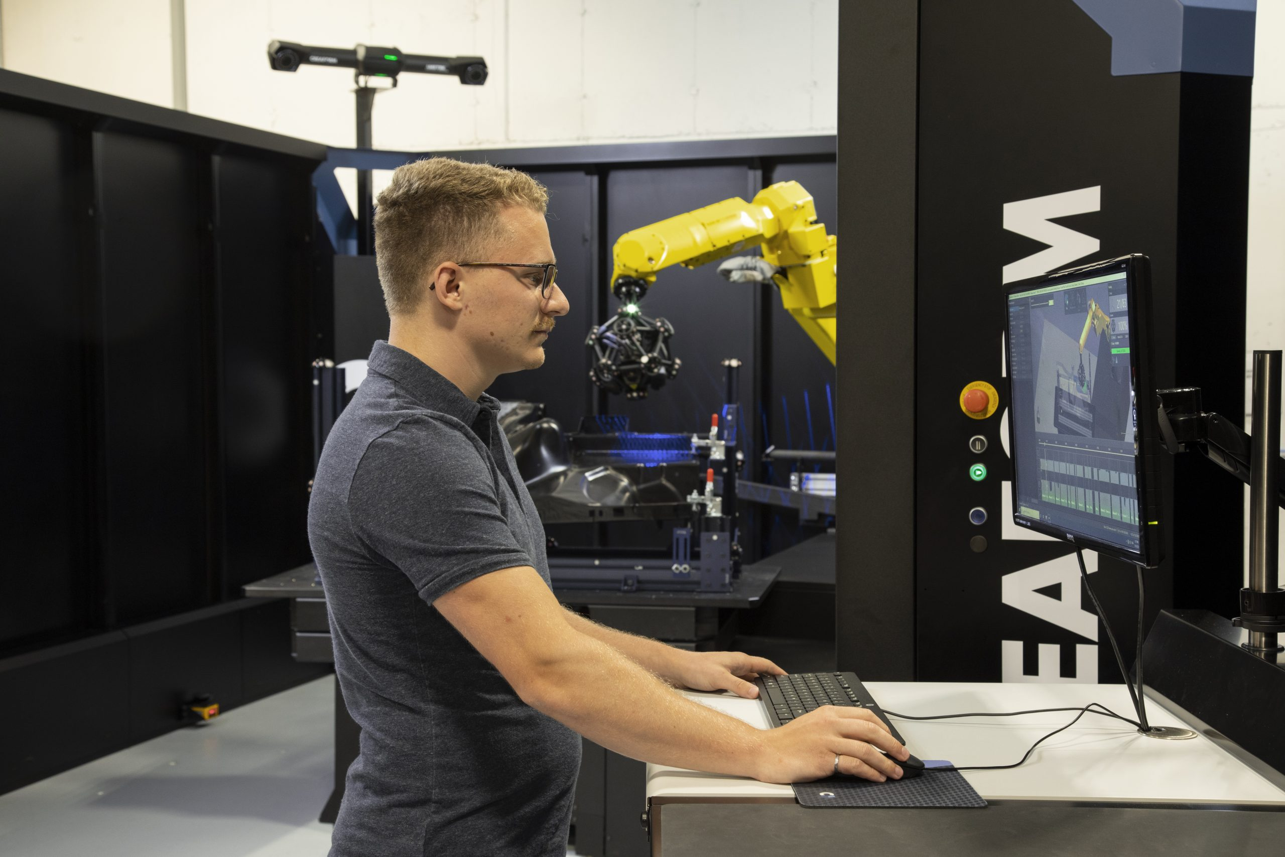 Man in front of computer screen with VXscan-R software controlling R-Series robot mounted MetraSCAN 3D with C-track scanning black bumper part