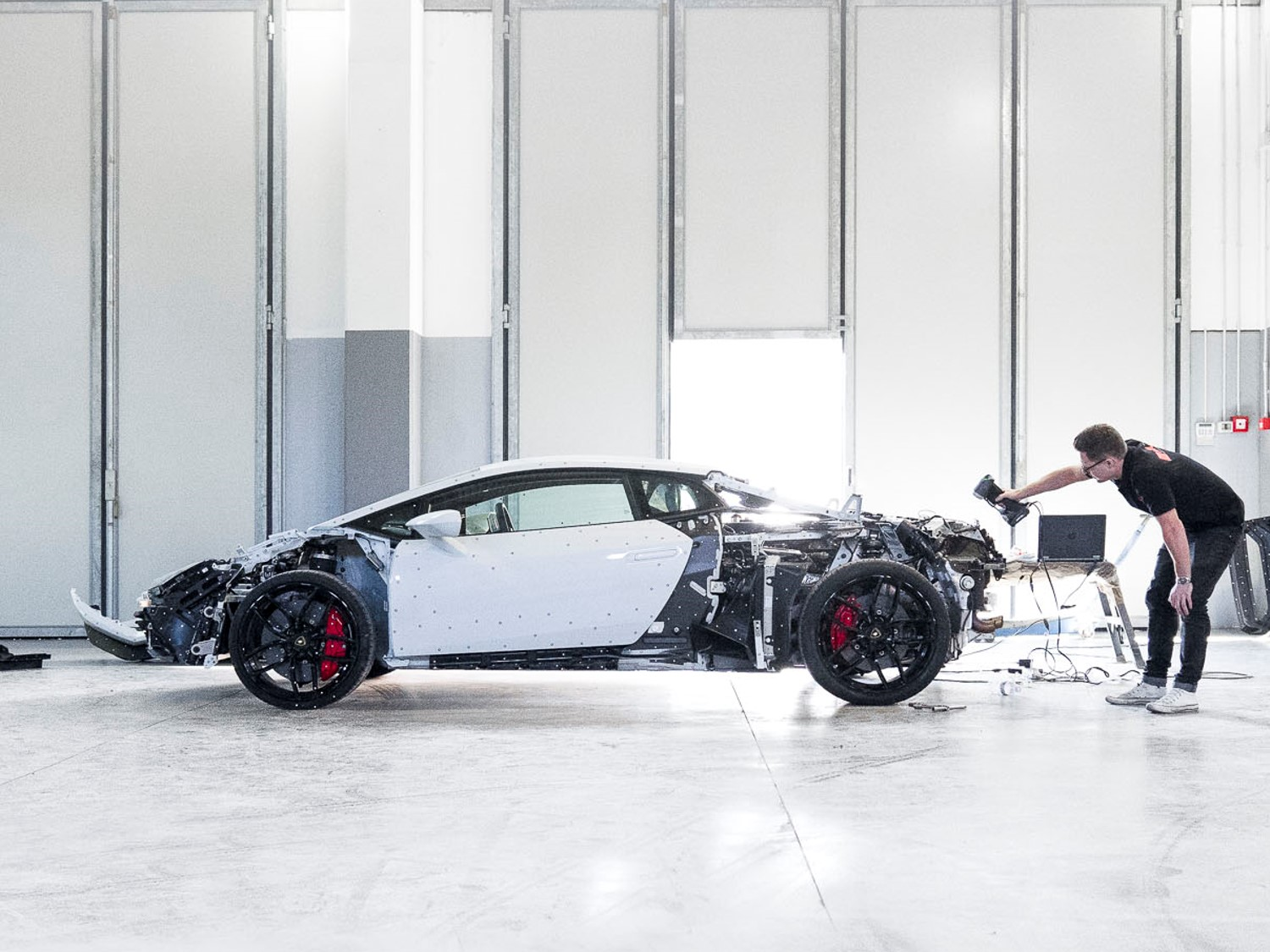 White Lamborghini Huracan in a workshop being scanned by employee with HandySCAN 3D scanner next to laptop