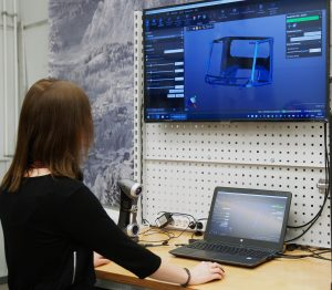 Employee working in VXelements on laptop and a second screen with HandySCAN 3D SILVER series scanner in the background
