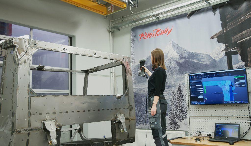 Employé utilisant un scanner de la série HandySCAN 3D SILVER pour numériser un châssis de la cabine de conducteur PistenBully devant un ordinateur