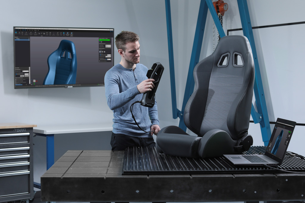 A white light structured light handheld 3D measurement system scanning a leather car seat in a metrology lab