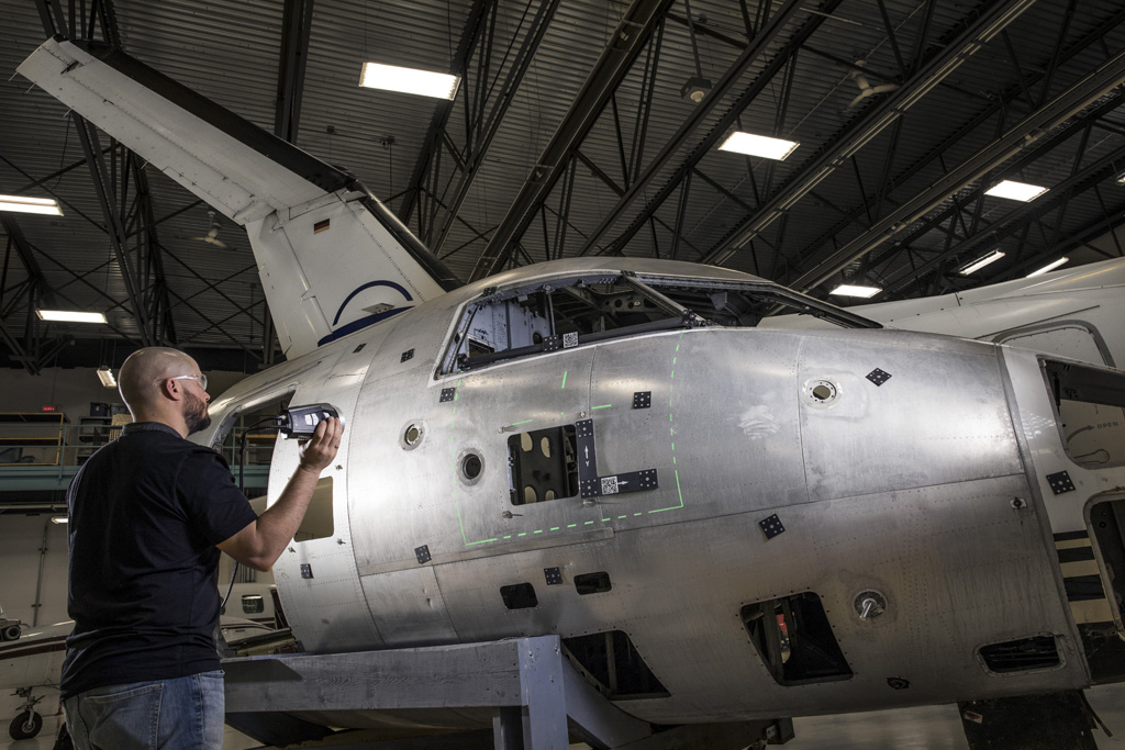 Portable photogrammetry camera system taking measurements on the cockpit and fuselage of a commercial airplane for quality control purposes