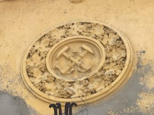 Sculpted family crest with hammers and grapes on yellow wall