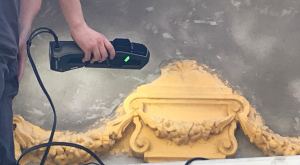 Man using Go!SCAN SPARK 3D to scan yellow wall sculpture details