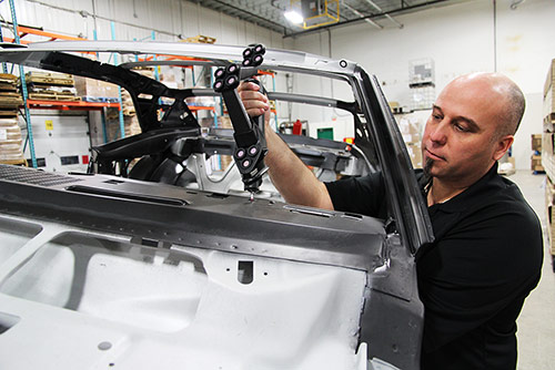 A metrologist performs a body car inspection in production floor