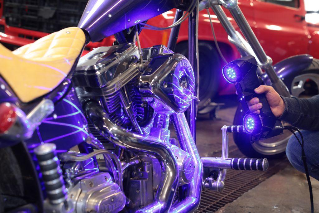 Der HandySCAN BLACK 3D scannt ein glänzendes Motorrad mittels seiner blauen Laser