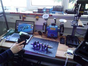 Pessoa usando um escâner 3D HandySCAN 3D BLACK Series para digitalizar um virabrequim em uma mesa ao lado de um laptop exibindo a digitalização no VXelements