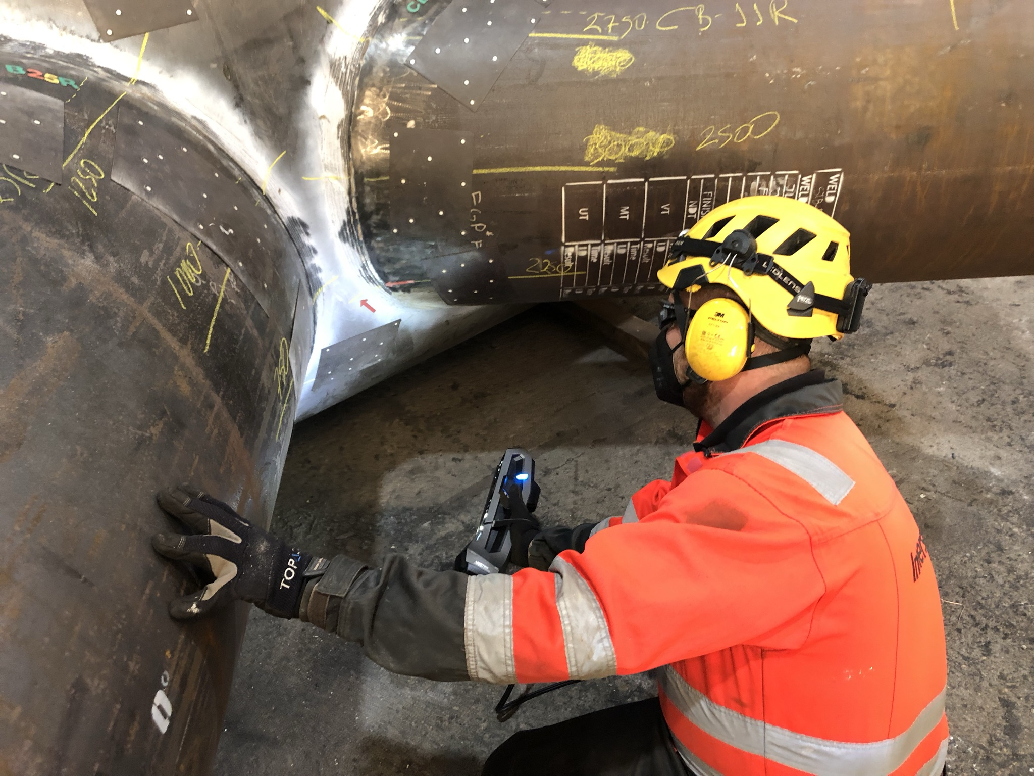 Innerspec employee scanning under pipe Junction with the Go!SCAN 3D