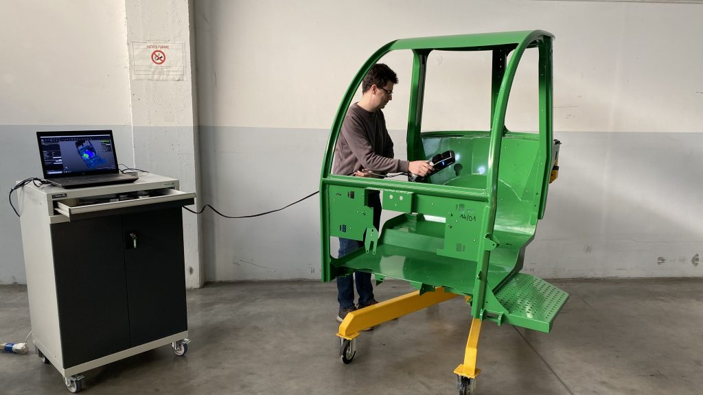 Man with Go!SCAN 3D scanning interior of green tractor cabin