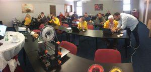 Sala de aula cheia de estudantes trabalhando em seus laptops com impressora 3D e vários objetos em primeiro plano