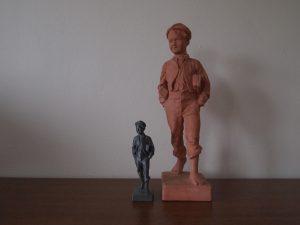 Estátua de um garote e um modelo impresso menor em 3D