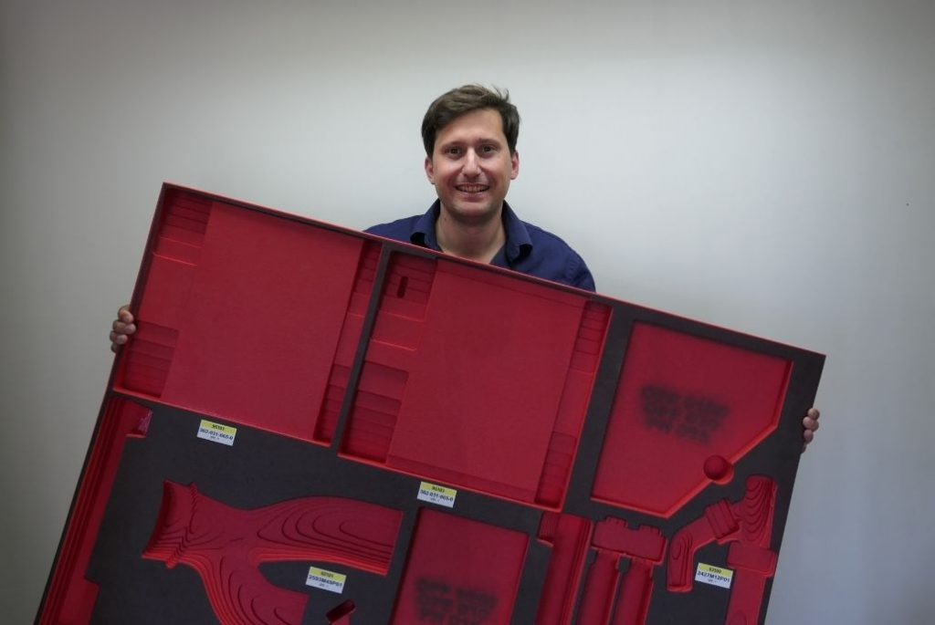 Oscar Llinares Manager of SkinPack holding a black and red kitting tray