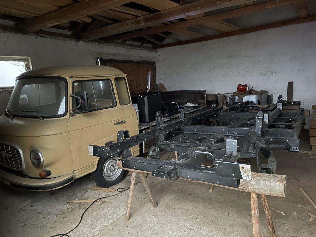 Vintage beige Barkas B1000 next to black car chassis on sawhorses