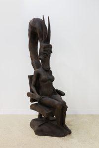 Estátua de uma mulher sentada com uma cobra engolindo sua cabeça