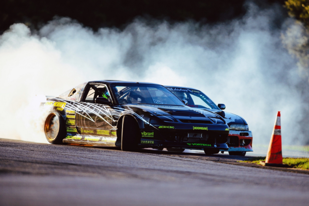 Two race cars drifting around a cone during a race with smoke behind