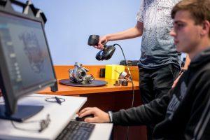 Aluno na frente do computador enquanto outro aluno usa o escâner ACADEMIA 50 para digitalizar um turbocompressor em uma mesa ao fundo
