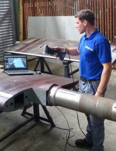 Voith employee in blue shirt using HandySCAN 3D SILVER to scan a large guide vane