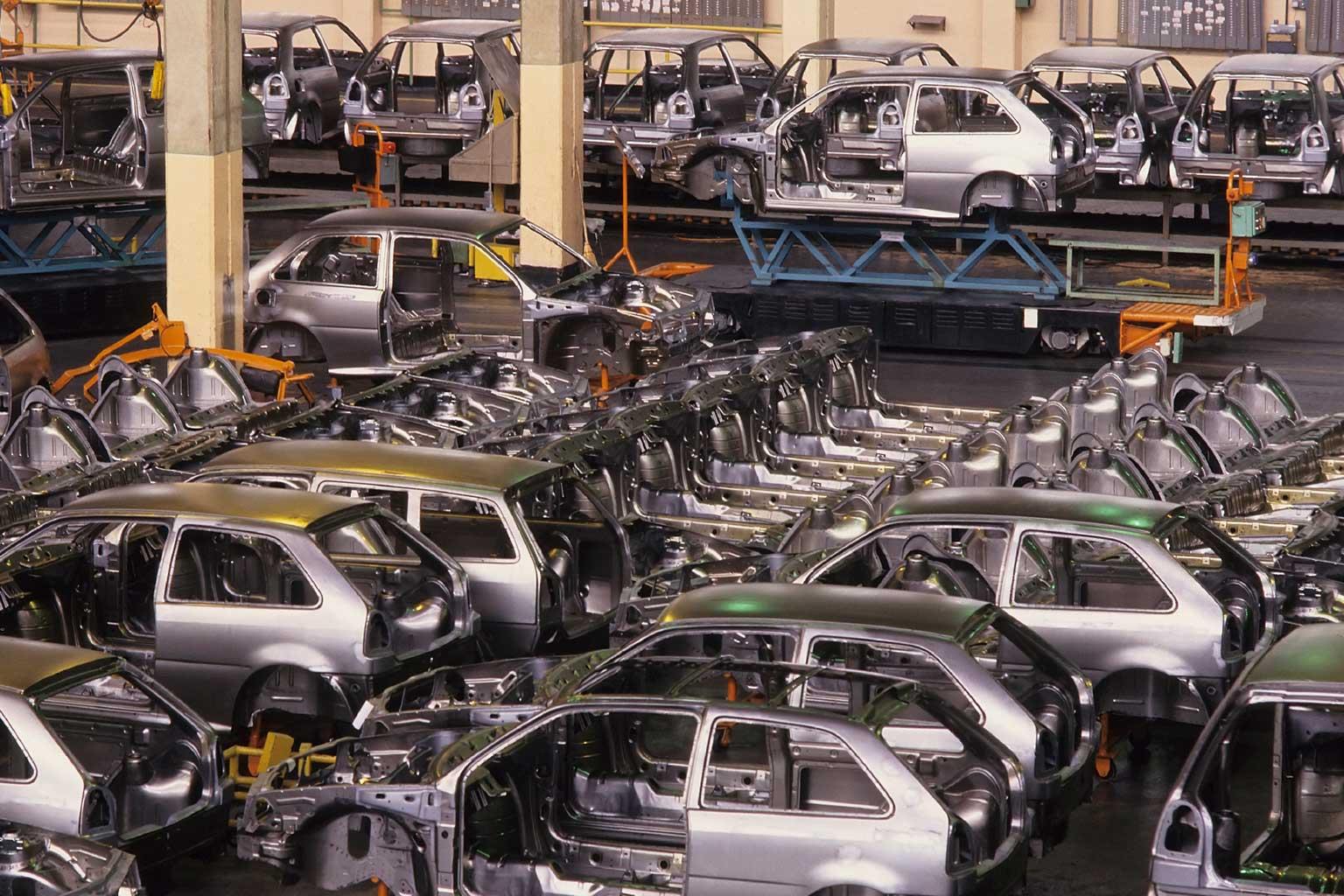 Diversi modelli di telai grigi di automobili accanto alla linea di produzione