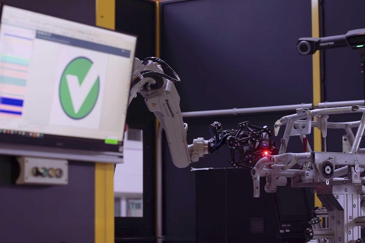 MetraSCAN montato su robot R-Series che esegue la scansione di un complesso assemblaggio tubolare accanto allo schermo del computer con un segno di spunta verde