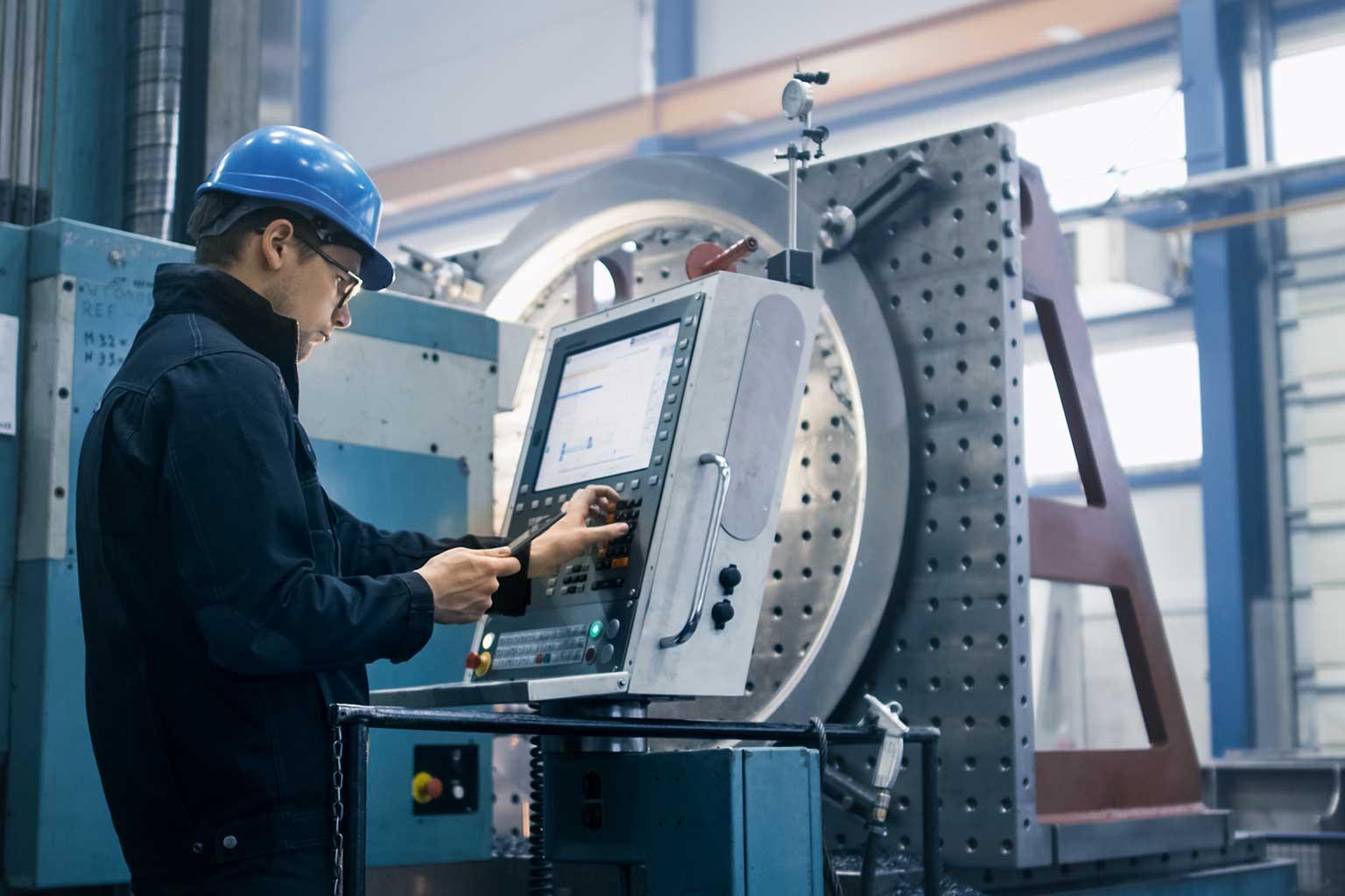 Operatore con elmetto blu che misura una parte rotonda di grandi dimensioni con una CMM tradizionale a contatto