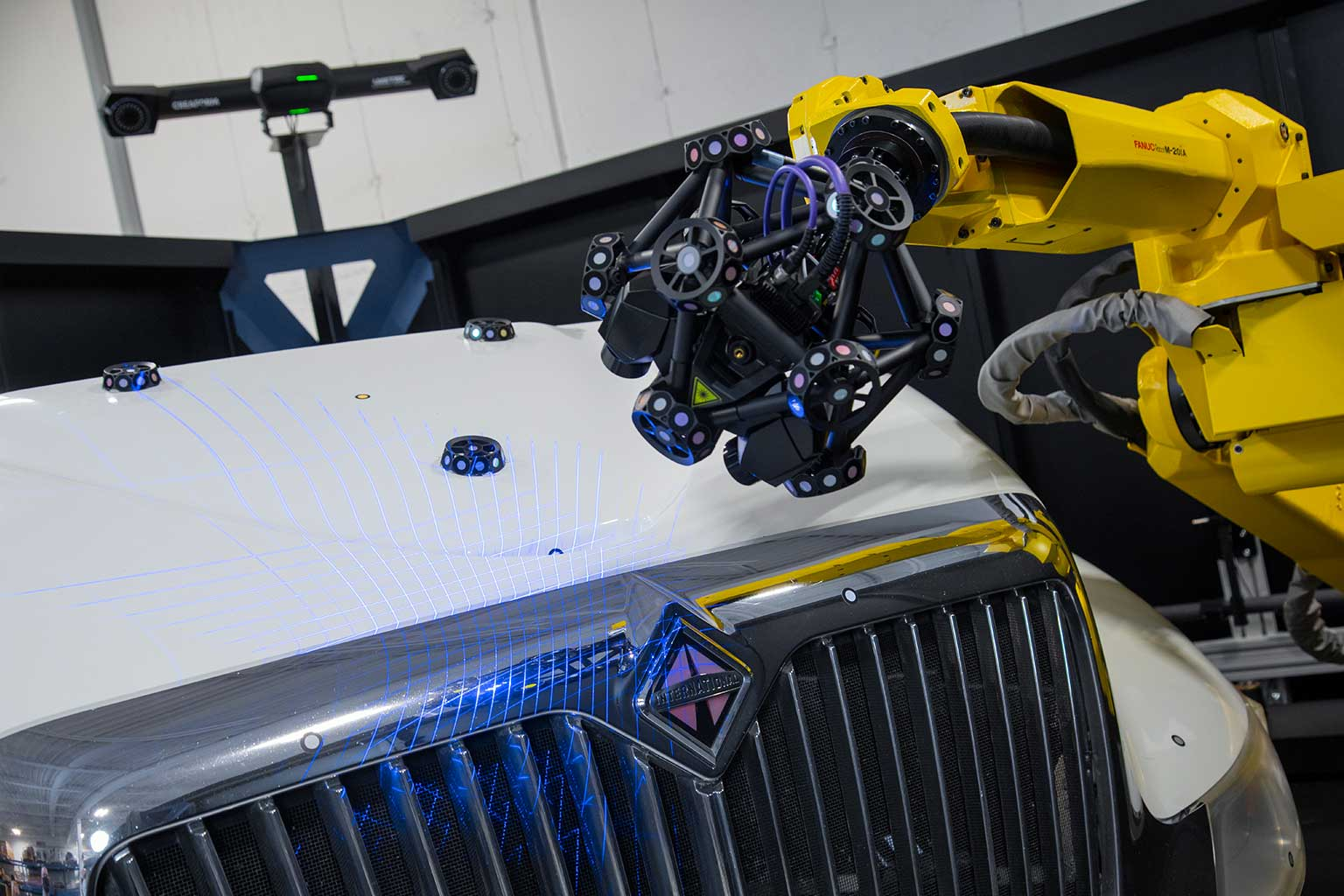 R-series robot mounted MetraSCAN 3D optical CMM scanning bumper and hood of white International truck with blue laser and C-track in background