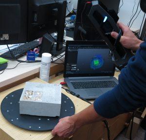 Pesquisador usando um escâner Go!SCAN 3D para digitalizar uma amostra de concreto em uma mesa na frente de um laptop