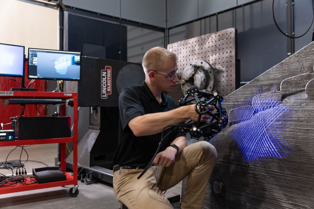 Lincoln Electric employee using the MetraSCAN 3D scanner to scan a large-scale metal 3D printing with computer on a mobile workstation in the background