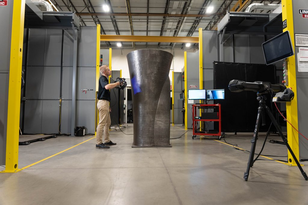 Alt text: Lincoln Electric employee using the MetraSCAN 3D scanner to scan a large-scale metal 3D printing with C-track in the foreground