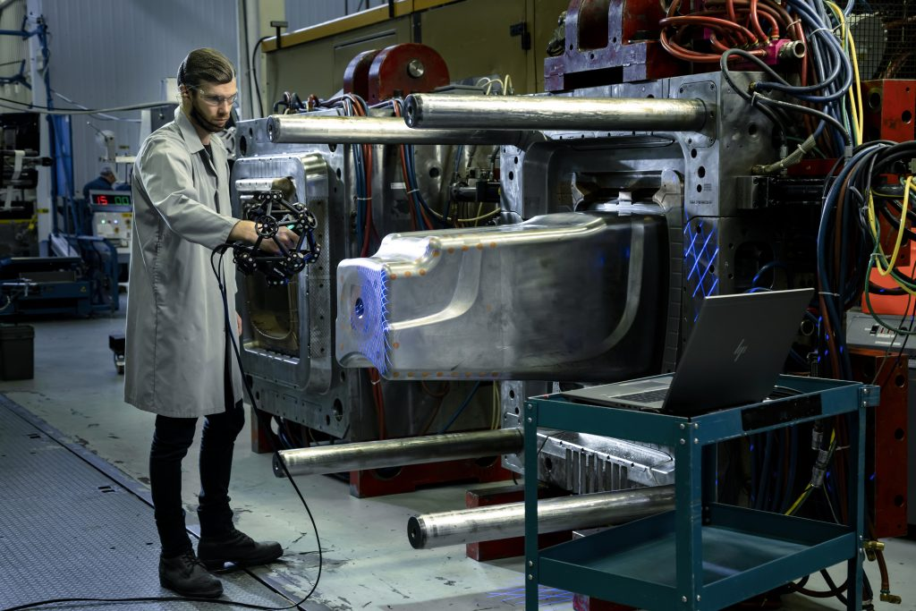 Metrology technician operating a blue light handheld 3d laser scanner on a large industrial mold in a factory environment