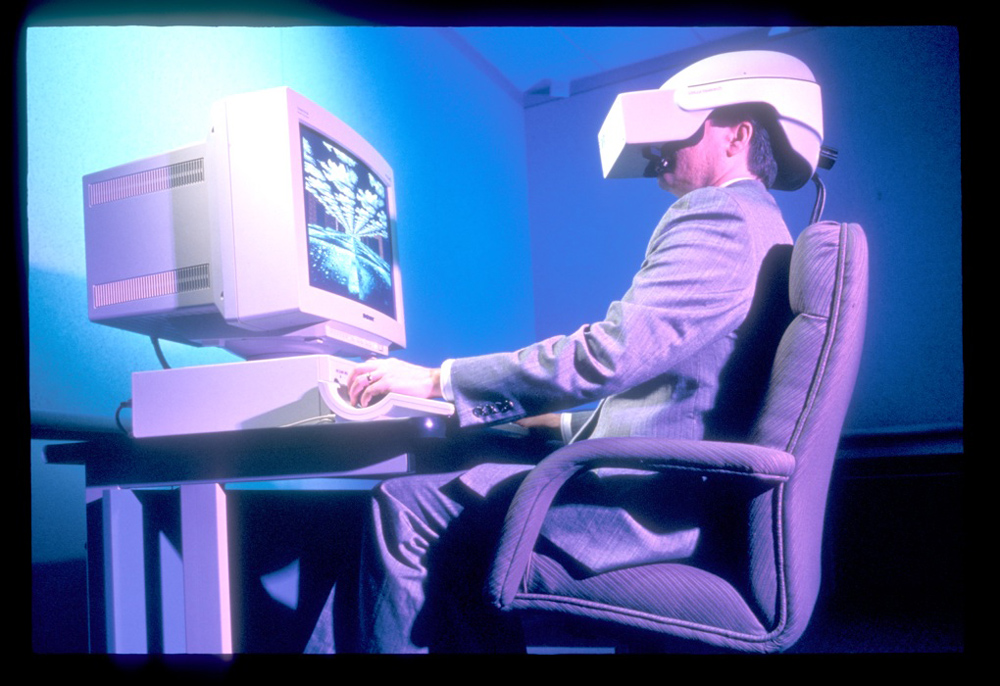 Men in front of computer with vintage virtual reality headset