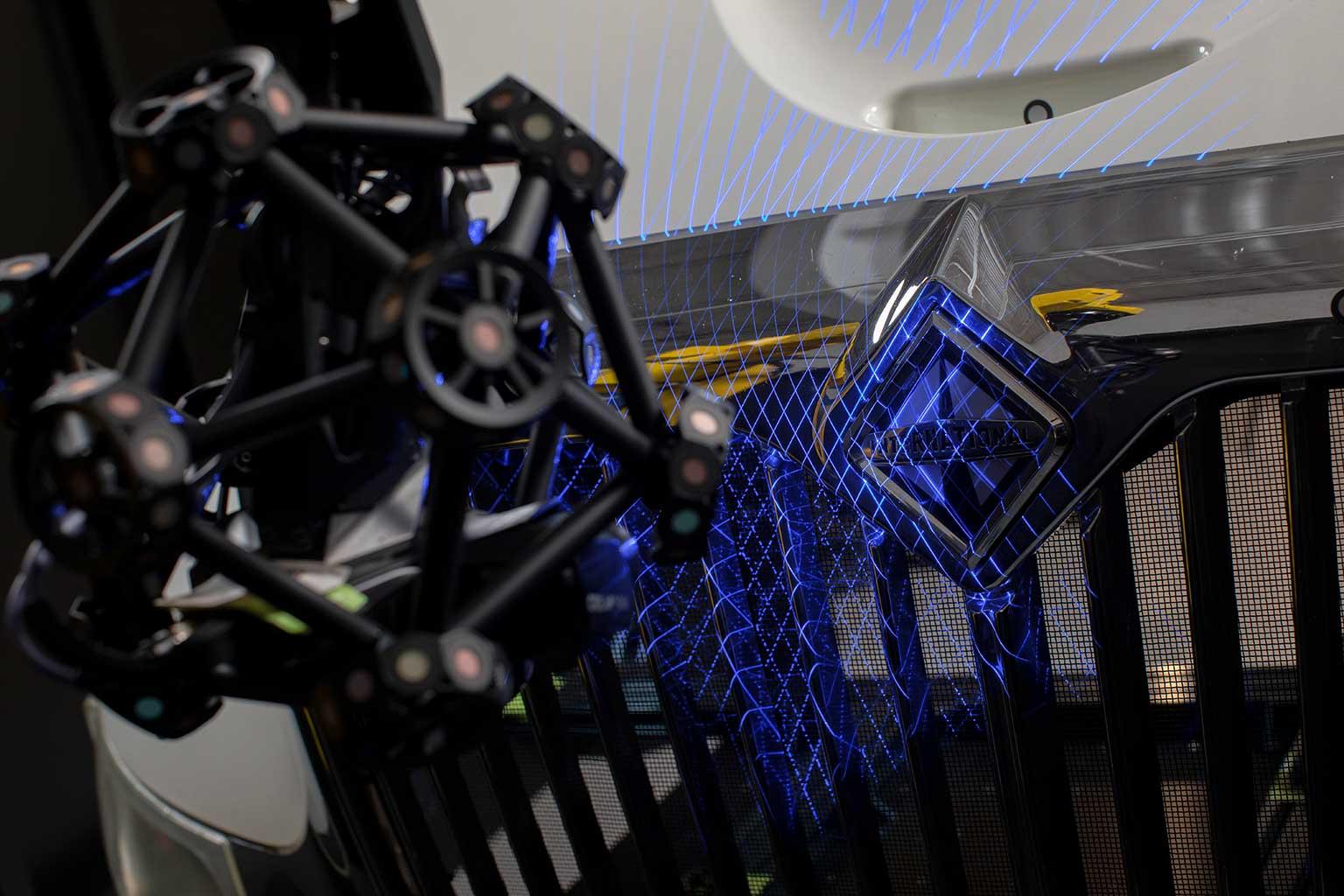R-series robot mounted MetraSCAN 3D optical CMM scanning shiny bumper and hood of white International truck
